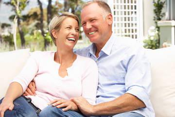 middle-aged couple smiling on beach l cosmetic dentistry lakeland fl